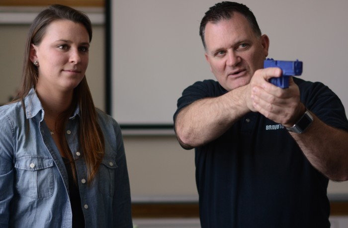 Kate Murphy watches as trainer Clark Aposhian demonstrates the proper use of a firearm for a teacher in a junior high classroom. Photo by: Jacob Byk